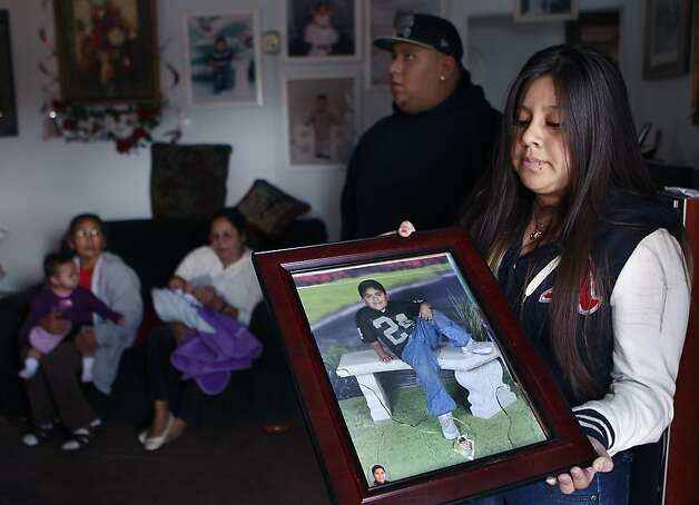 Angelina Duenas, 13, holds a damaged photograph of her younger brother, 11-year-old Luis, who was hit by a bullet that traveled through three walls in a drive-by shooting in Oakland, Calif. on Thursday, Sept. 20, 2012. One of the bullets pierced the portrait of Luis (below), when gunmen pumped several rounds into the home at about 1 a.m. Photo: Paul Chinn, The Chronicle
