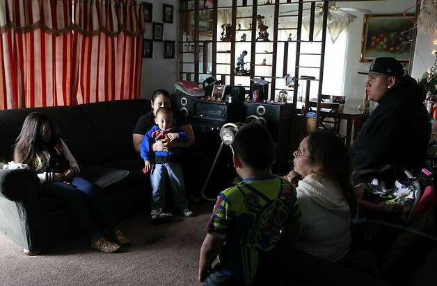 Family members gather in the living room after 11-year-old Luis Duenas was hit by a bullet that traveled through three walls in a drive-by shooting in Oakland, Calif. on Thursday, Sept. 20, 2012. Luis was sleeping in his bed when gunmen pumped several rounds into the home at about 1 a.m. Photo: Paul Chinn, The Chronicle