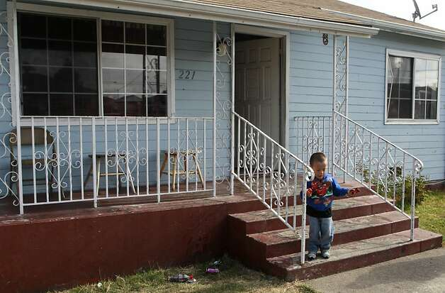 Rodolfo Del Real, 3, plays on the front porch after his 11-year-old cousin, Luis Duenas, was injured by a bullet that traveled through three walls in a drive-by shooting in Oakland, Calif. on Thursday, Sept. 20, 2012. Luis was sleeping in his bed when gunmen pumped several rounds into the home at about 1 a.m. Photo: Paul Chinn, The Chronicle
