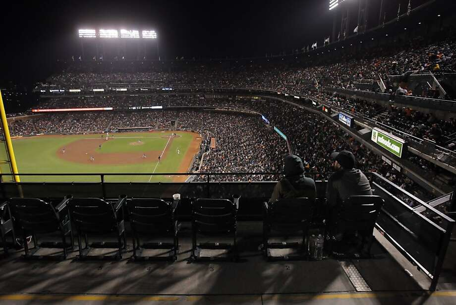 Jon and Louise Barcellos of Oakland watch Wednesday night's Giants-Rockies game alongside empty seats. Photo: Carlos Avila Gonzalez - San Fran, The Chronicle