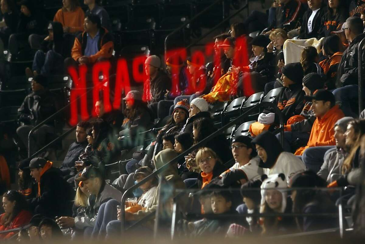 The AT&T sign is reflected in a stairwell plexiglass panel with Giants fans watching the game in the background. The San Francisco Giants' streak of sellouts at AT&T Park is well over 150 games now. Given that there are visible empty seats at the games, is the stadium really full?