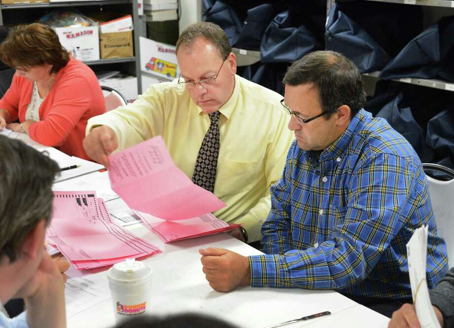 Democratic Commissioner Edward McDonough, left, and Republican Commissioner Larry Bugbee count absentee ballots in the McDonald-Marchione primary at the Rensselaer Co. Board of Election in Troy Thursday Sept. 20, 2012.  (John Carl D'Annibale / Times Union) Photo: John Carl D'Annibale / 00019347A