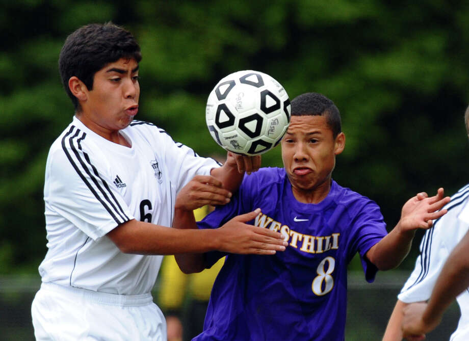 Trumbull's #6 Alberto Aguilon, left, and Westhill's #8 Octavio Avila go after the ball, during boys soccer action in Trumbull, Conn. on Thursday September 20, 2012. Photo: Christian Abraham / Connecticut Post