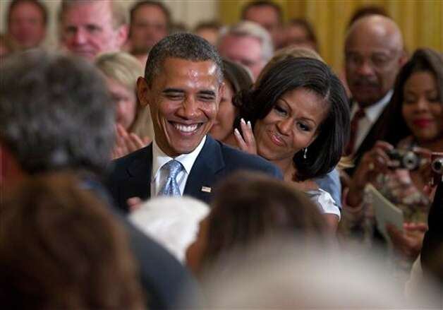 President Barack Obama and first lady Michelle Obama applaud former President George H.W. Bush and former first lady Barbara Bush, not seen, during the portrait unveiling ceremony for former President George W. Bush and former first lady Laura Bush portraits, Thursday, May 31, 2012, in the East Room of the White House in Washington. Photo: Carolyn Kaster, AP / AP