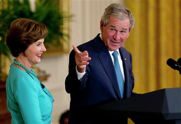 Former President George W. Bush, accompanied by former first lady Laura Bush, gestures in the East Room of the White House in Washington, Thursday, May 31, 2012, during a ceremony to unveil  their  portraits. (AP Photo/Carolyn Kaster)† Photo: Carolyn Kaster, AP / AP