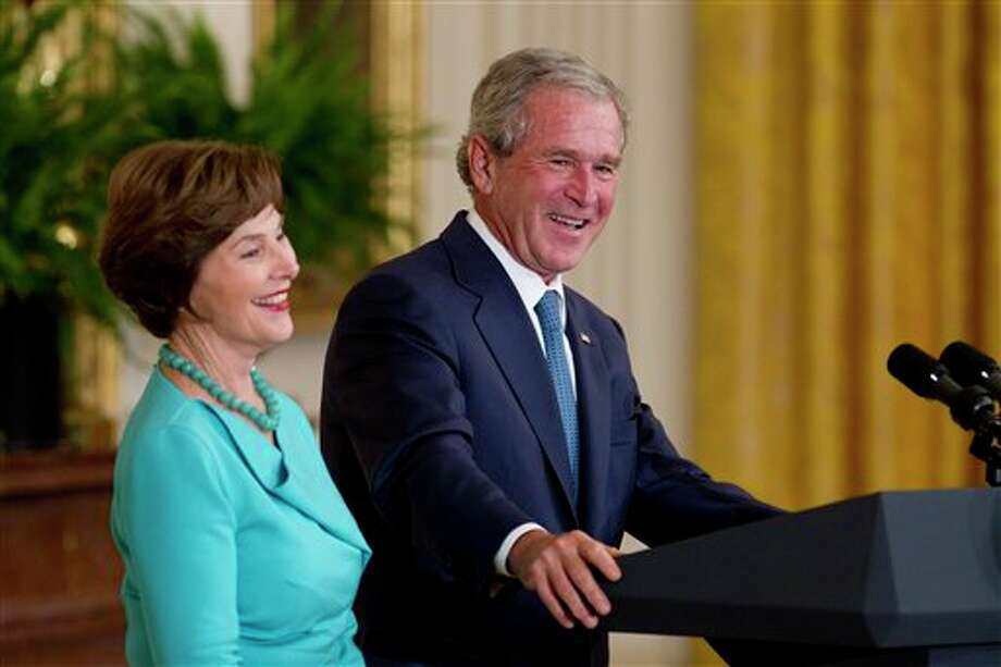 Former President George W. Bush and former first lady Laura Bush stand together on stage during a ceremony to unveil their portraits in the East Room of the White House in Washington, Thursday, May 31,2012. Photo: Carolyn Kaster, AP / AP