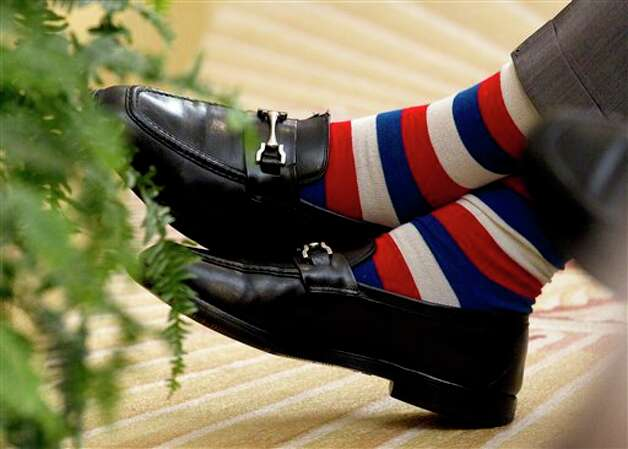 Former President George H.W. Bush crosses his red white and blue socked feet during the unveiling ceremony of former President George W. Bush, his son, and former first lady Laura Bush's portraits, Thursday, May 31, 2012, in the East Room of the White House in Washington. Photo: Carolyn Kaster, AP / AP