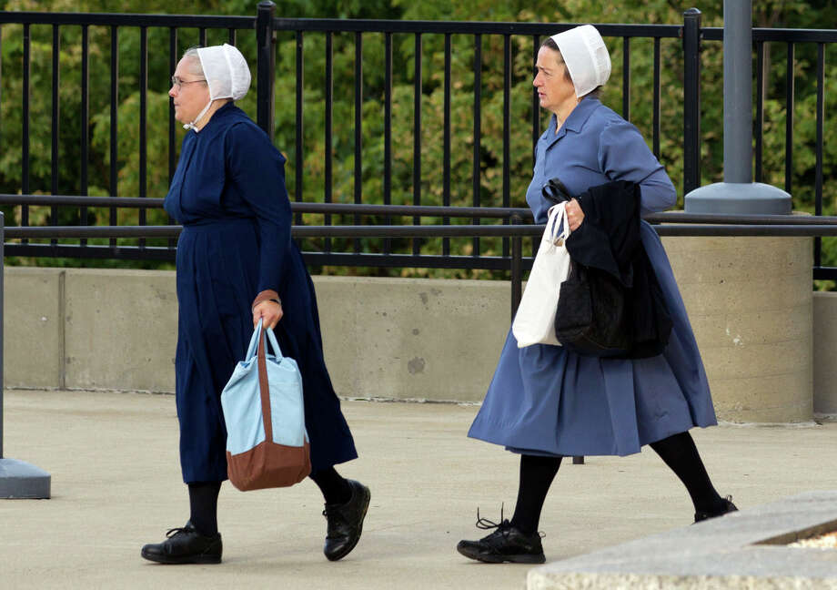 Two Amish women walk to the U.S. Federal Courthouse in Cleveland on Thursday, Sept. 20, 2012.  The jury will begin their fifth day of deliberations in the trial of 16 Amish people accused of hate crimes in hair- and beard-cutting attacks against fellow Amish in Ohio. (AP Photo/Scott R. Galvin) Photo: Scott R. Galvin