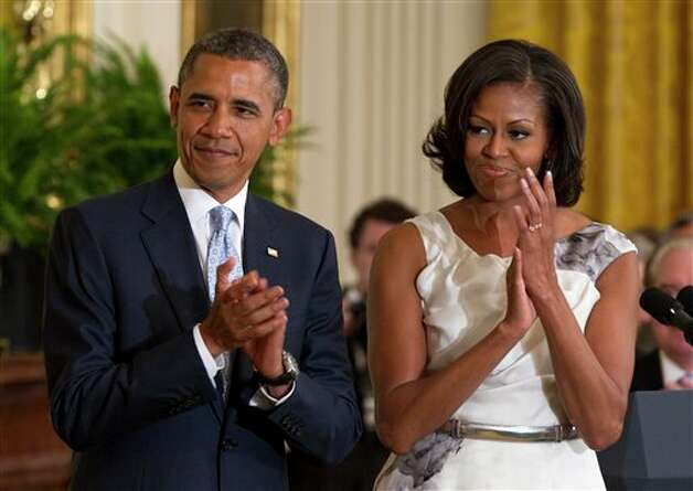 President Barack Obama and first lady Michelle Obama applaud in the East Room of the White House in Washington, Thursday, May 31, 2012, during a ceremony to unveil portraits of former President George W. Bush and former first lady Laura Bush.  (AP Photo/Carolyn Kaster) (AP)
