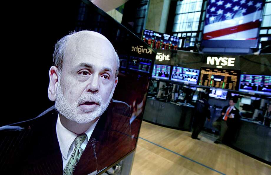 FILE-In this Thursday, June 7, 2012, file photo, Federal Reserve Chairman Ben Bernanke appears on a television screen on the floor of the New York Stock Exchange. Americans' wealth dipped about 0.5 percent in the April-June quarter as a drop in stock prices more than offset a gain in home values. Yet since June, a resurgent stock market has jumped about 7 percent; more than reversing last quarter's 3 percent drop in stock prices. (AP Photo/Richard Drew, File) Photo: Richard Drew