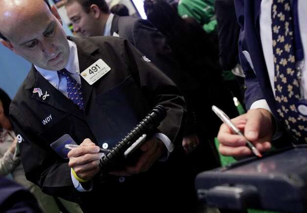 Trader Andrew Silverman, left, works on the floor of the New York Stock Exchange Thursday, Sept. 20, 2012. Stocks are opening lower on Wall Street after the government reported that more people applied for unemployment benefits last week than economists had been expecting. (AP Photo/Richard Drew) Photo: Richard Drew