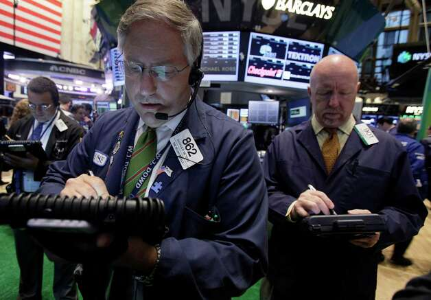 Warren Meyers, center, works with fellow traders on the floor of the New York Stock Exchange, Thursday, Sept. 20, 2012. Stocks are opening lower on Wall Street after the government reported that more people applied for unemployment benefits last week than economists had been expecting. (AP Photo/Richard Drew) Photo: Richard Drew