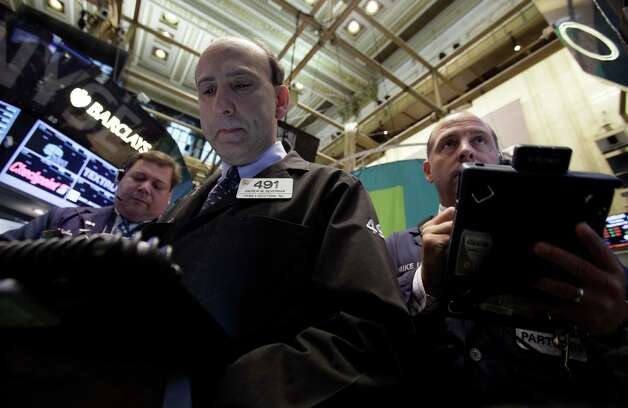 Trader Andrew Silverman, center, works on the floor of the New York Stock Exchange Thursday, Sept. 20, 2012. Stocks are opening lower on Wall Street after the government reported that more people applied for unemployment benefits last week than economists had been expecting. (AP Photo/Richard Drew) Photo: Richard Drew