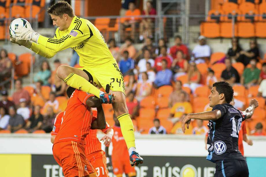 Houston Dynamo goalkeeper Tyler Deric (24) tumbles over teammate Warren Creavalle (5) as C.D. FAS forward Ricardo Ulloa looks on during the first half of a CONCACAF Champions League match on Thursday, Sept. 20, 2012, at BBVA Compass Stadium in Houston. Photo: Smiley N. Pool, Houston Chronicle / © 2012  Houston Chronicle