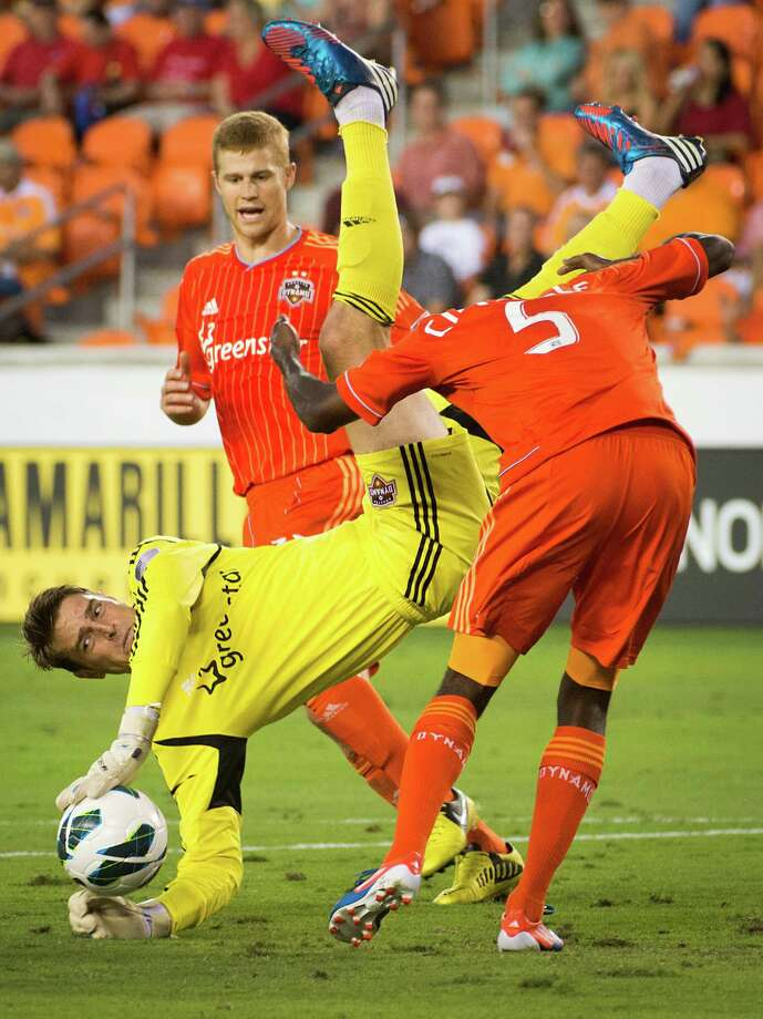 Houston Dynamo goalkeeper Tyler Deric (24) tumbles over teammate Warren Creavalle (5)  during the first half of a CONCACAF Champions League match against C.D. FAS on Thursday, Sept. 20, 2012, at BBVA Compass Stadium in Houston. Photo: Smiley N. Pool, Houston Chronicle / © 2012  Houston Chronicle