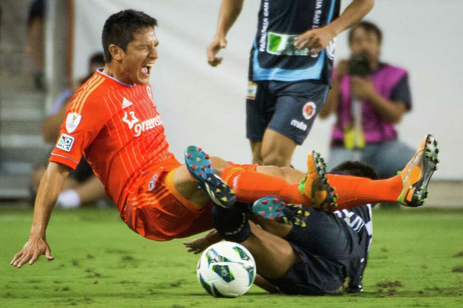 Houston Dynamo forward Brian Ching is taken out on a tackle by C.D. FAS defender Alex Mendoza during the first half of a CONCACAF Champions League match on Thursday, Sept. 20, 2012, at BBVA Compass Stadium in Houston. Photo: Smiley N. Pool, Houston Chronicle / © 2012  Houston Chronicle