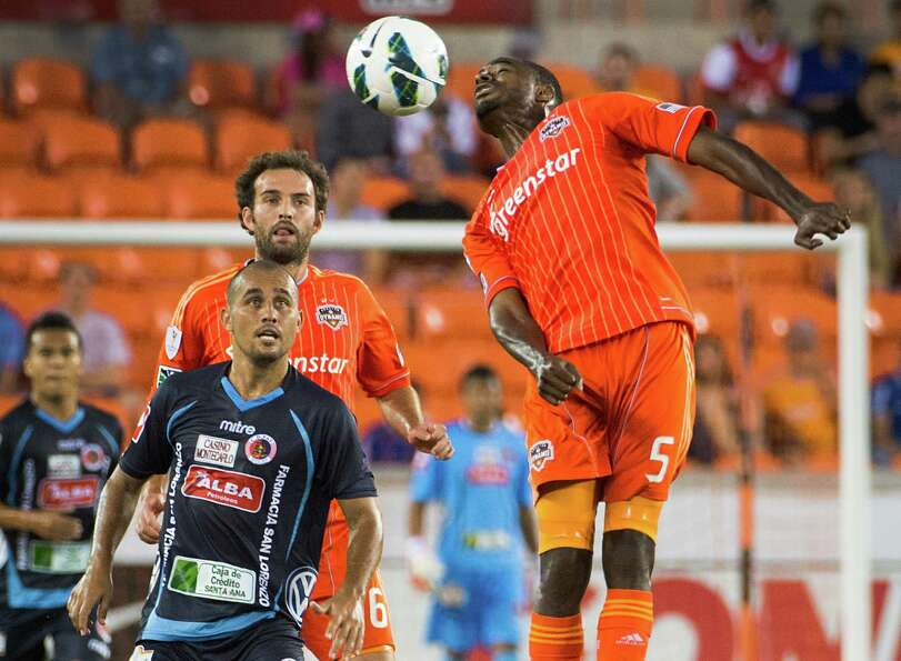 Houston Dynamo defender Warren Creavalle (5) wins a header as C.D. FAS midfielder Emerson Luiz looks