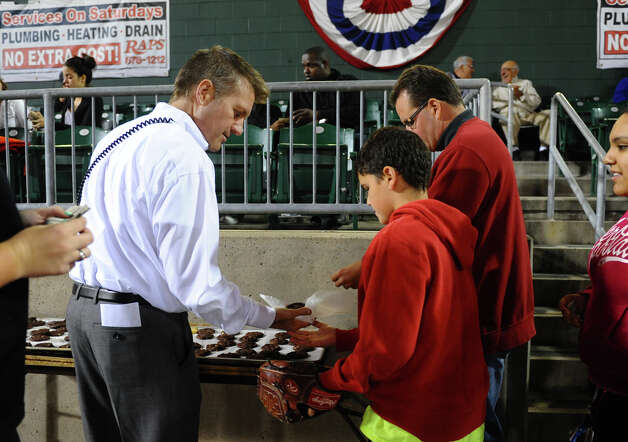 Bluefish baseball's new GM Ken Shepard, left, hands out cookies to fans for a dollar each, between the fourth inning of baseball action against Lancaster at the Ball Park at Harbor Yard in Bridgeport, Conn. on Thursday September 20, 2012. Photo: Christian Abraham / Connecticut Post
