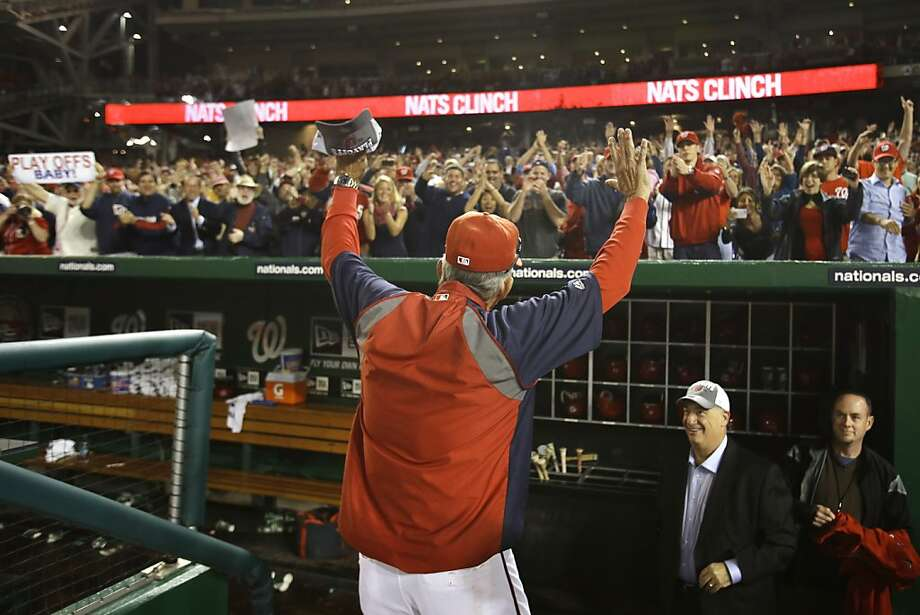 Manager Davey Johnson, right, saluted the fans as he left the field and the team wore caps acknowledging the playoff berth. Photo: Jacquelyn Martin, Associated Press