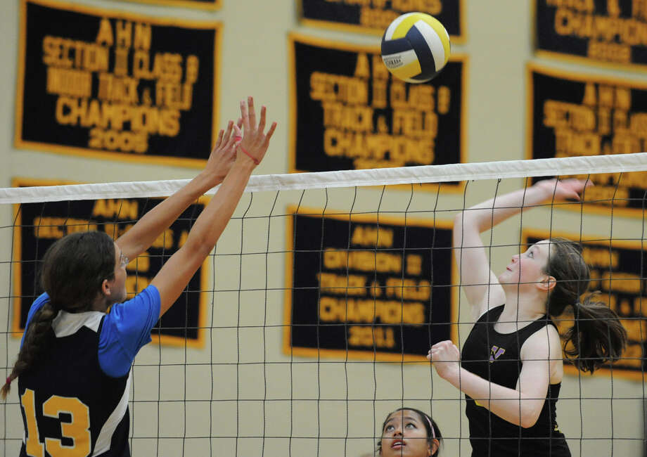 From left, Academy of the Holy Names' Kerry Losert tries to stop Voorheesville's Emma Sprotbery from hitting the ball over the net during a volleyball match Thursday, Sept. 20, 2012 in Albany, N.Y. (Lori Van Buren / Times Union) Photo: Lori Van Buren