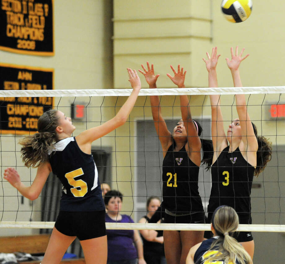 From left, Academy of the Holy Names' Mary O'Toole hits one past Voorheesville's Libby Bjork and Caroline Balin during a volleyball match Thursday, Sept. 20, 2012 in Albany, N.Y. (Lori Van Buren / Times Union) Photo: Lori Van Buren