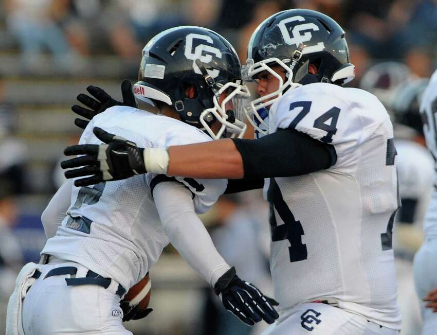 LaShawn Thomas, left, of Central Catholic is embraced by teammate Andrew Campbell after a first-half touchdown during high-school football action at Alamo Stadium on Thursday, Sept. 20, 2012.