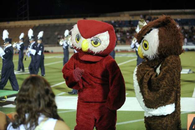 The Highlands High School Owl mascots converse on the sidelines at Alamo Stadium on Thursday, Sept. 20, 2012. Photo: Billy Calzada, Express-News / © San Antonio Express-News