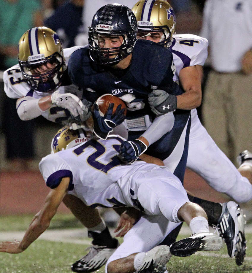 Charger receiver Michael Moloney is sandwiched by tacklers as Champion hosts Marble Falls at Boerne Stadium on September 20, 2012. Photo: Tom Reel, Express-News / ©2012 San Antono Express-News