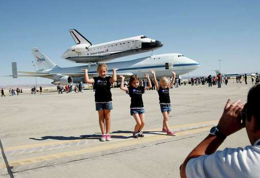 Ashely Olson, left, poses with her sisters, Alexis, center, and Alyssa in front of the Space Shuttle Endeavour at the NASA Dryden Flight Research Center at Edwards Air Force Base, Calif., Thursday, Sept. 20, 2012. Endeavour returned to its California roots after a wistful cross-country journey that paid homage to NASA workers and former Arizona Rep. Gabrielle Giffords and her astronaut husband. Photo: Jae C. Hong, Associated Press / AP