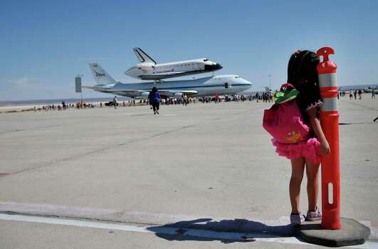 Elizabeth Danirjian, 5, of Santa Clarita, Calif., looks at Space Shuttle Endeavour mounted on NASA's Shuttle Carrier Aircraft (SCA) after it landed at the NASA Dryden Flight Research Center at Edwards Air Force Base, Calif., Thursday, Sept. 20, 2012. Endeavour returned to its California roots after a wistful cross-country journey that paid homage to NASA workers and former Arizona Rep. Gabrielle Giffords and her astronaut husband. Photo: Jae C. Hong, Associated Press / AP
