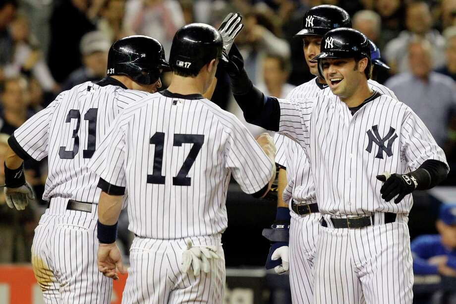 New York Yankees' Ichiro Suzuki (31), Jayson Nix (17) and Derek Jeter, rear right, congratulate Nick Swisher, right, on his fourth-inning grand slam off Toronto Blue Jays relief pitcher Brad Lincoln in their baseball game at Yankee Stadium in New York, Thursday, Sept. 20, 2012. (AP Photo/Kathy Willens) Photo: Kathy Willens