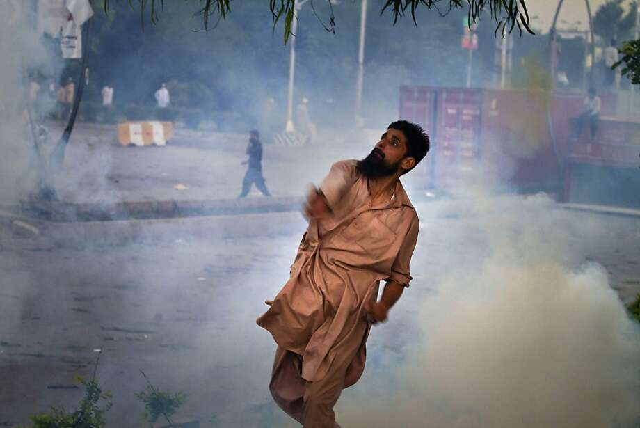 A Pakistani protester hurls back a tear gas canister fired by police, not pictured, during clashes that erupted as protestors tried to approach the U.S. embassy, in Islamabad, Pakistan, Thursday, Sept. 20, 2012. Hundreds of Pakistanis angry at an anti-Islam film that denigrates the religion's prophet clashed with police in the Pakistani capital Thursday, the most violent show of anger in a day that saw smaller demonstrations in Indonesia, Iran and Afghanistan. (AP Photo/Anjum Naveed) Photo: Anjum Naveed, Associated Press