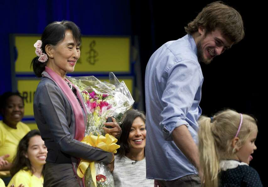 Aung San Suu Kyi of Myanmar smiles after receiving flowers from Petr Verzilov (2nd R) and his daught
