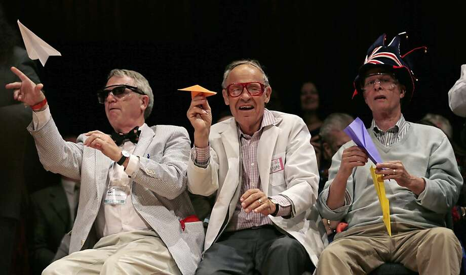 CORRECTS TO REFLECT THAT KIRSHNER IS NOT A NOBEL LAUREATE, ADDS HIS CURRENT TITLE - Harvard University Clowes Professor of Science Robert Kirshner, left, along with Nobel laureates Dudley Herschbach, center, and Rich Roberts, fire paper airplanes back at the audience during a performance at the Ig Nobel Prize ceremony at Harvard University, in Cambridge, Mass., Thursday, Sept. 20, 2012. The Ig Nobel prize is an award handed out by the Annals of Improbable Research magazine for silly sounding scientific discoveries that often have surprisingly practical applications.(AP Photo/Charles Krupa) Photo: Charles Krupa, Associated Press