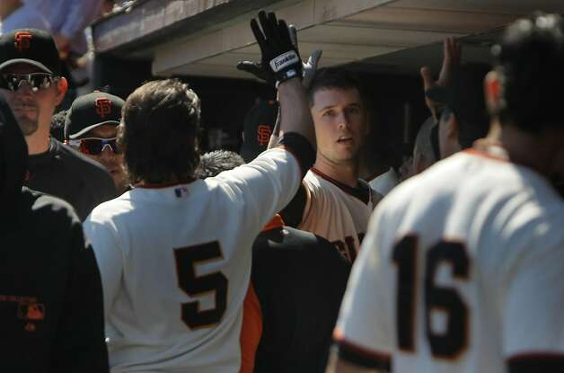 The Giants' Buster Posey  celebrates his homerun in the fourth inning with teammates. The San Francisco Giants played the Colorado Rockies at AT&T Park  on Thursday,  September 20, 2012 in San Francisco, Calif. Final Score: San Francisco Giants: 9 - Colorado Rockies: 2 Photo: Lea Suzuki, The Chronicle