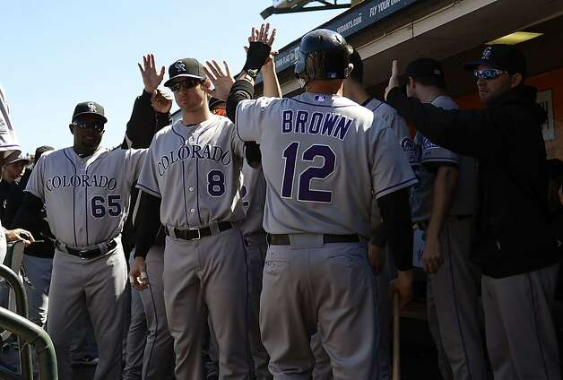 SAN FRANCISCO, CA - SEPTEMBER 20:  Andrew Brown #12 of the Colorado Rockies is congraturlated by teammates after Brown scored in the fourth innng against the San Francisco Giants at AT&T Park on September 20, 2012 in San Francisco, California.  (Photo by Thearon W. Henderson/Getty Images) Photo: Thearon W. Henderson, Getty Images