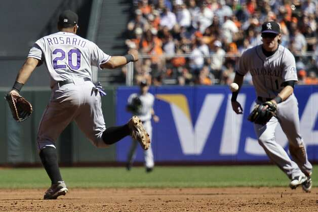 Colorado Rockies first baseman Wilin Rosario, left, misses a fly ball hit by San Francisco Giants' Pablo Sandoval as second baseman Josh Rutledge, right, watches during the third inning of their baseball game in San Francisco, Thursday, Sept. 20, 2012. Rosario was given an error and the Giants scored a run on the play. (AP Photo/Eric Risberg) Photo: Eric Risberg, Associated Press