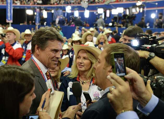 Former Republican presidential candidate and current Texas Governor Rick Perry (L) speaks to the media at the Tampa Bay Times Forum in Tampa, Florida, on August 28, 2012 during the Republican National Convention. The 2012 Republican National Convention is expected to host 2,286 delegates and 2,125 alternate delegates from all 50 states, the District of Columbia and five territories.  (ROBYN BECK / AFP/Getty Images) Photo: ROBYN BECK, AFP/Getty Images / AFP