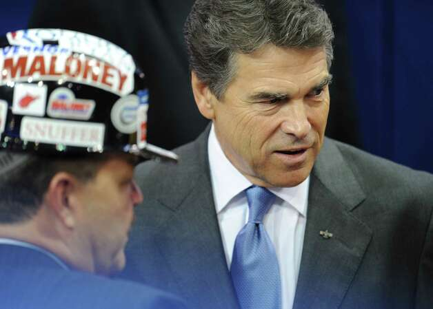 Former presidential candidate Rick Perry arrives at the Tampa Bay Times Forum in Tampa, Florida, on August 30, 2012 on the final day of the Republican National Convention (RNC). The RNC will culminate later today with the formal nomination of Mitt Romney and Paul Ryan as the GOP presidential and vice-presidential candidates in the US presidential election.   (ROBYN BECK / AFP/Getty Images) Photo: ROBYN BECK, AFP/Getty Images / AFP
