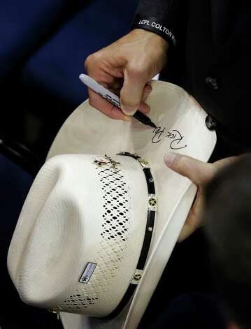 Texas Governor Rick Perry signs a delegates cowboy hat during the Republican National Convention in Tampa, Fla., on Thursday, Aug. 30, 2012.  (Charlie Neibergall / Associated Press) Photo: Charlie Neibergall, Associated Press / AP