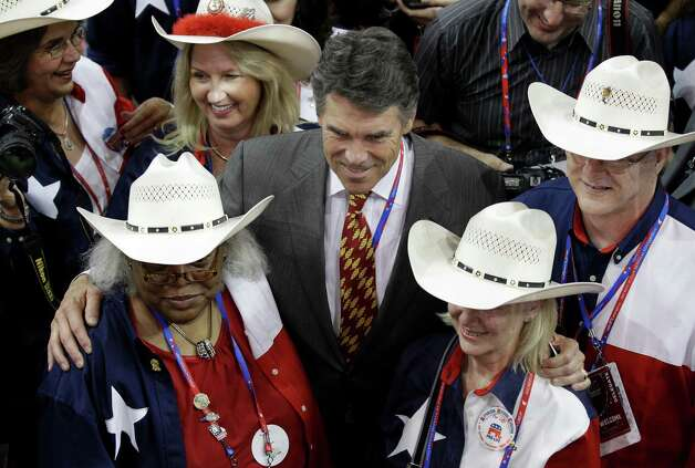 Texas Governor Rick Perry poses with delegates during the Republican National Convention in Tampa, Fla., on Tuesday, Aug. 28, 2012.  (Charlie Neibergall / Associated Press) Photo: Charlie Neibergall, Associated Press / AP
