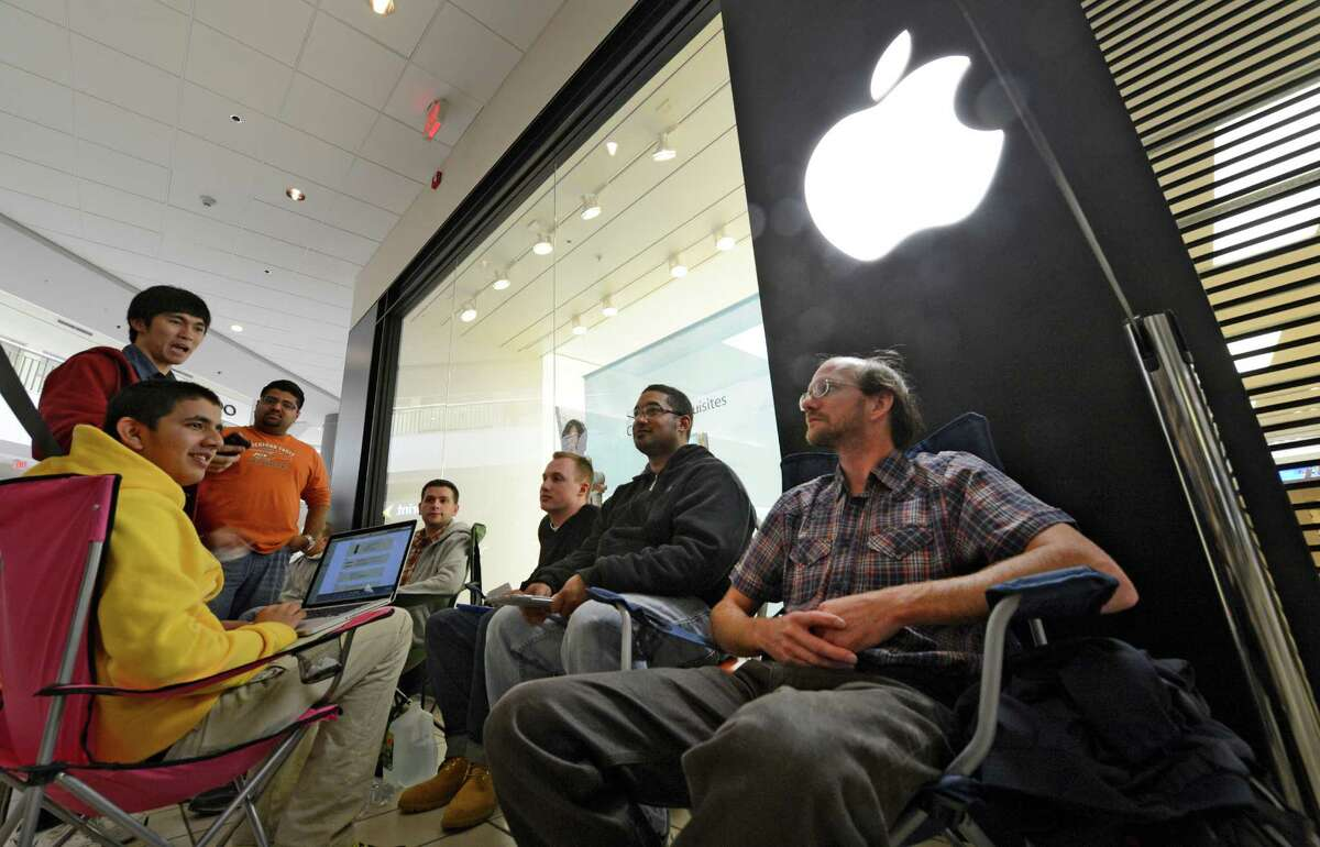 Brian Wheeler sat under the Apple logo from 9:20 P.M. last evening to be first in line at the Apple Store in Crossgates Mall in Guilderland, N.Y to receive his IPhone 5 Sept. 21, 2012. Wheeler was also the first in line to purchase the IPhone 4S. (Skip Dickstein/Times Union)