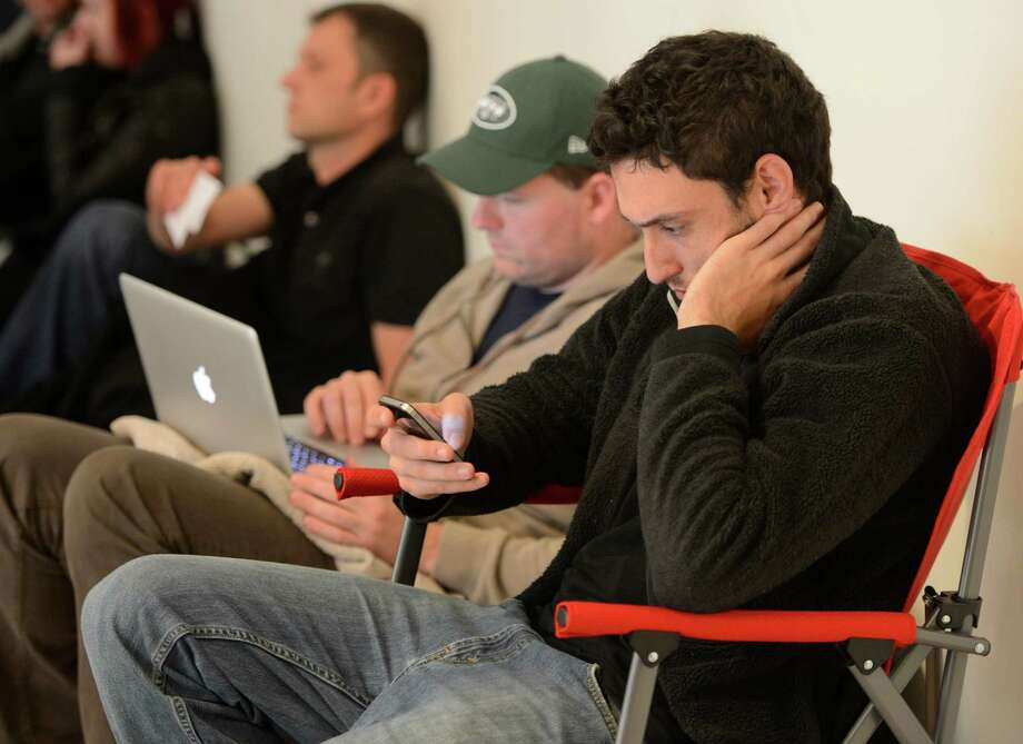 Ian Hunter, owner of a restaurant in Troy uses his older Iphone outside the Apple Store in Crossgates Mall in Guilderland, N.Y  while he waits for his chance to purchase  the IPhone 5 Sept. 21, 2012.   (Skip Dickstein/Times Union) Photo: Skip Dickstein