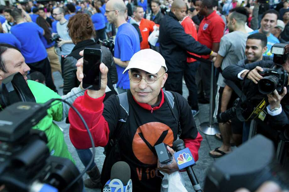 Hazem Sayed, 54, the first in line to purchase the new iPhone 5, holds up his new phone in front of media outside the Fifth Avenue Apple store, Friday, Sept. 21, 2012, in New York. Hundreds of people waited in line through the early morning to be among the first to get their hands on the highly anticipated phone. (AP Photo/John Minchillo) Photo: John Minchillo, Associated Press / FR170537 AP