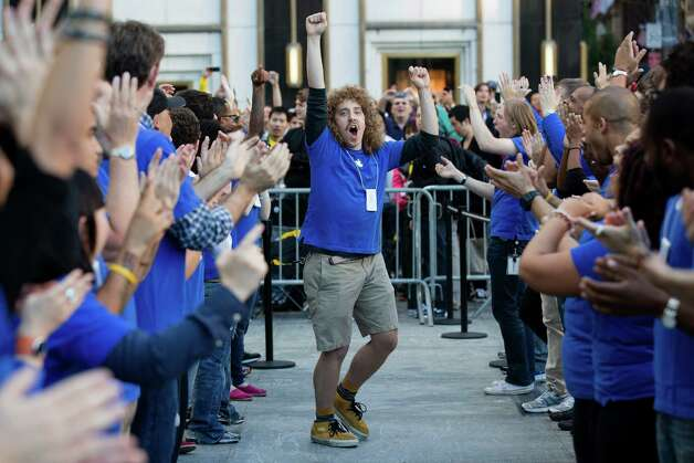 An Apple employee riles up his coworkers outside the Fifth Avenue Apple store to celebrate the release of the iPhone 5, Friday, Sept. 21, 2012, in New York. Hundreds of people waited in line through the early morning to be among the first to get their hands on the highly anticipated phone. (AP Photo/John Minchillo) Photo: John Minchillo, Associated Press / FR170537 AP