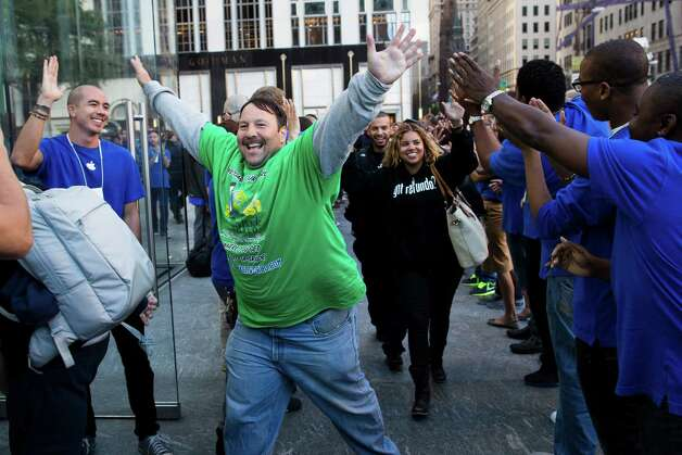 Greg Packer, 49, celebrates as he enters the Fifth Avenue Apple store for the release of the iPhone 5, Friday, Sept. 21, 2012, in New York. Hundreds of people waited in line through the early morning to be among the first to get their hands on the highly anticipated phone. (AP Photo/John Minchillo) Photo: John Minchillo, Associated Press / FR170537 AP