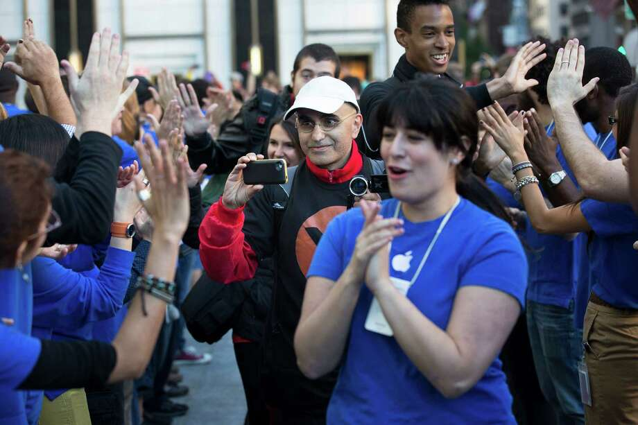 Hazem Sayed, 54, the first in line to purchase the new iPhone 5, takes pictures outside the Fifth Avenue Apple store, Friday, Sept. 21, 2012, in New York. Hundreds of people waited in line through the early morning to be among the first to get their hands on the highly anticipated phone. (AP Photo/John Minchillo) Photo: John Minchillo, Associated Press / FR170537 AP