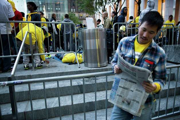 A consumer leans against a barricade while waiting in line outside the Fifth Avenue Apple store for the imminent release of the iPhone 5, Friday, Sept. 21, 2012, in New York. Hundreds of people waited in line through the early morning to be among the first to get their hands on the highly anticipated phone. (AP Photo/John Minchillo) Photo: John Minchillo, Associated Press / FR170537 AP
