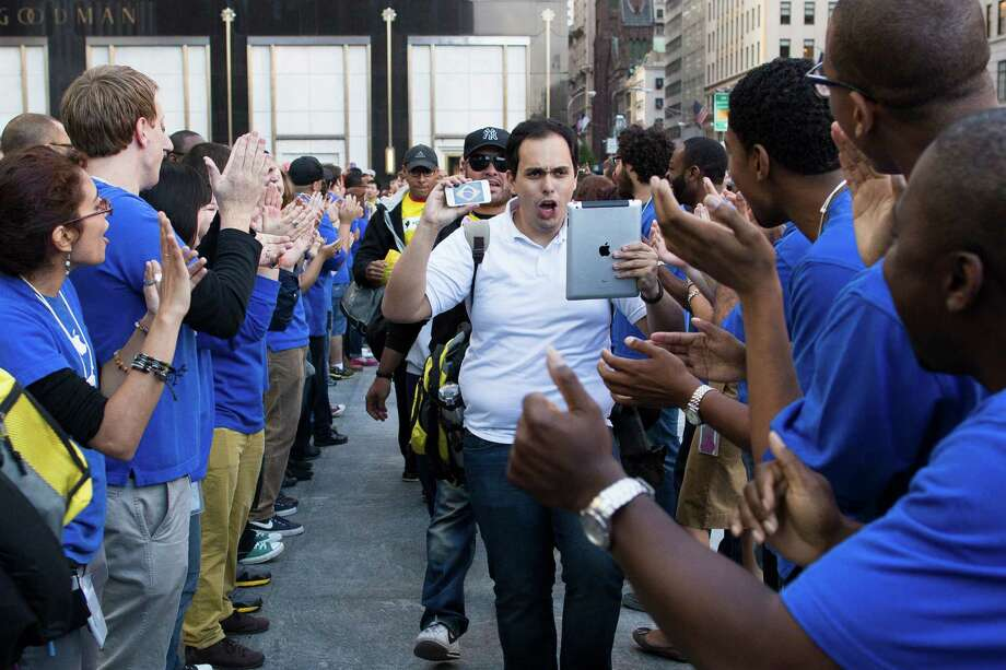 A consumer captures the celebration on his Apple products as he enters the Fifth Avenue Apple store for the release of the iPhone 5, Friday, Sept. 21, 2012, in New York. Hundreds of people waited in line through the early morning to be among the first to get their hands on the highly anticipated phone. (AP Photo/John Minchillo) Photo: John Minchillo, Associated Press / FR170537 AP