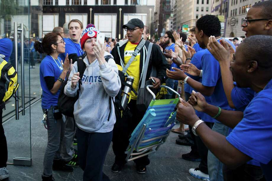A consumer captures the celebration on her Apple products as she enters the Fifth Avenue Apple store for the release of the iPhone 5, Friday, Sept. 21, 2012, in New York. Hundreds of people waited in line through the early morning to be among the first to get their hands on the highly anticipated phone. (AP Photo/John Minchillo) Photo: John Minchillo, Associated Press / FR170537 AP